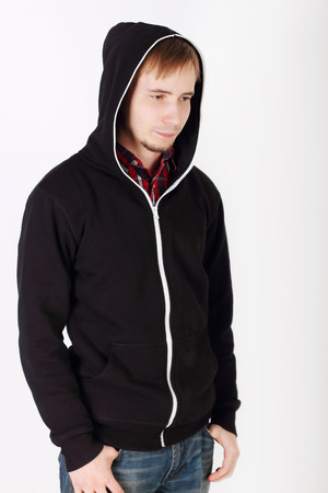 Young sad handsome man in black hoodies and jeans looks away photo