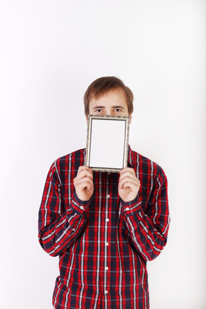 hides: Young man with beard in checkered red shirt hides his mouth behind frame