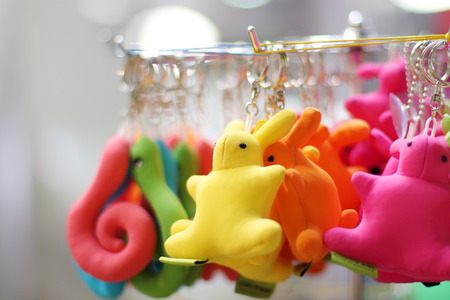 key fob: Small soft multicolored bunnies and snakes keychains hang in shop. Shallow dof Stock Photo