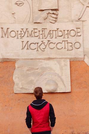 monumental: Back of man in red vest looking on embossed lettering Monumental art