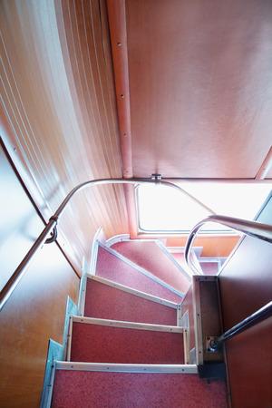 Descend down angular stairway in English double-decker bus