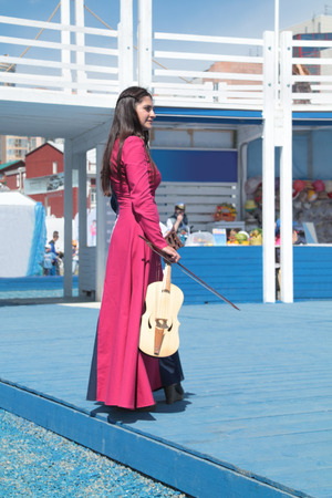 nights: PERM, RUSSIA - JUN 11, 2013: Busker girl in long red dress with violin in hand stands on stage at festival White Nights in Perm