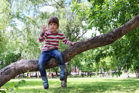 enthusiastically: Pretty happy girl in striped sweater and jeans waves hand sitting on the tree on sunny day