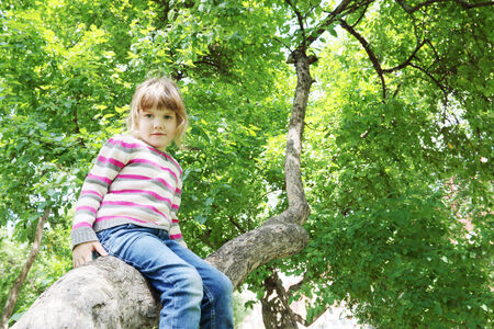 enthusiastically: Girl in striped sweater sitting on tree trunk and looking at camera