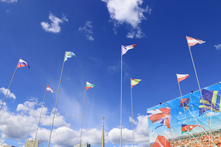 PERM, RUSSIA - JUNE 25, 2014: Triangular flags of different countries on background of blue sky at festival White Nights