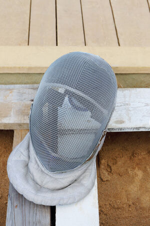 fencing wire: Grey Mask for fencing made of steel wire on wooden boards and sand closeup