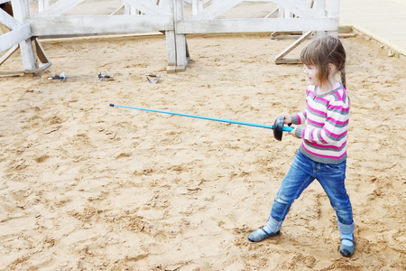 rapier: Pretty little happy girl standing on sand with blue rapier training for fencing