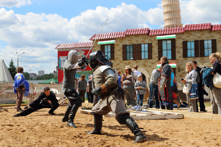 nights: PERM, RUSSIA - JUNE 25, 2014: Two swordsman fighting with swords on sand at festival White Nights