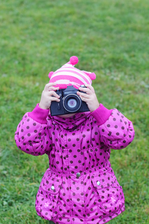 rarity: Little girl in pink photographs by camera rarity outdoors at autumn day