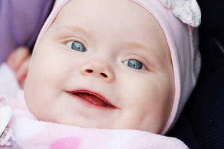 Closeup of beautiful cute little girl is in carriage and smiling photo