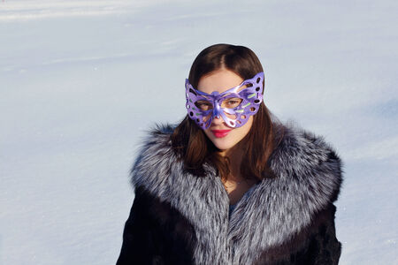 furskin: Beautiful girl in fur coat and mask at background of snow in sunny winter day