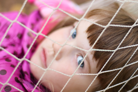 bonnet up: Littlt cute girl looks through white grid hammock. Shallow dof. Focus on net