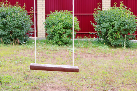 Close up of wooden swing with rope and green bushes in background Stock Photo