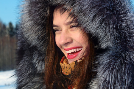 Beautiful girl in fur coat with hood laughs outdoor in sunny winter day photo