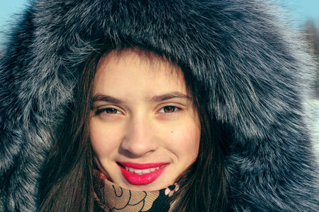 Beautiful girl in fur coat with hood smiles and looks at camera in sunny winter day photo