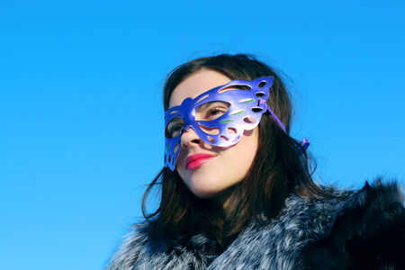 furskin: Beautiful girl in fur coat and mask looks away in sunny winter day