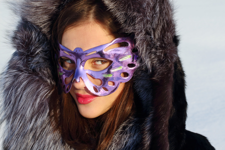 Beautiful girl in fur coat and mask looks away sideways in sunny winter day