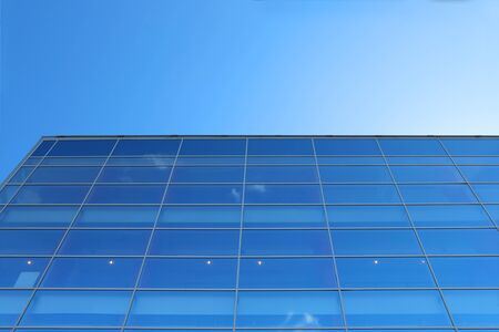 wall clouds: Glass wall of building with reflection of blue sky with small clouds Stock Photo