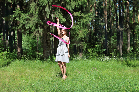 Beautiful girl in dress is engaged in rhythmic gymnastics with ribbon on grass on sunny day photo