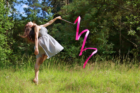 Beautiful girl in dress is engaged in rhythmic gymnastics with ribbon in clearing in woods