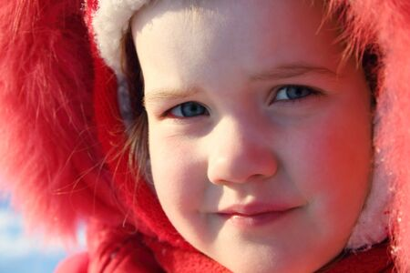 fur hood: Little girl in red warm fur hood looks at camera at winter sunny day