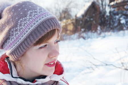 Portrait of young beautiful woman looking away at winter day in village photo