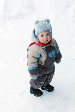 jumpsuit: Little boy wearing warm jumpsuit stands on snow and smiles at winter