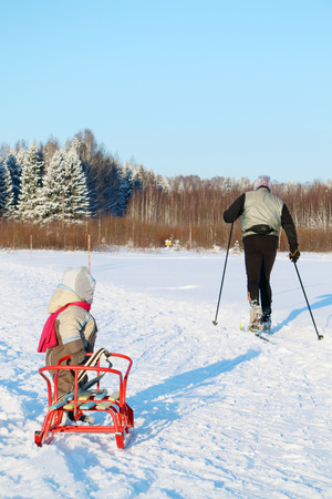 jumpsuit: Little boy in warm jumpsuit with sled looks at skier near forest at winter