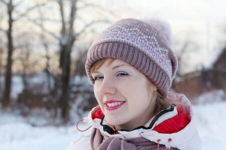 Portrait of young happy woman looking away at winter day in village photo