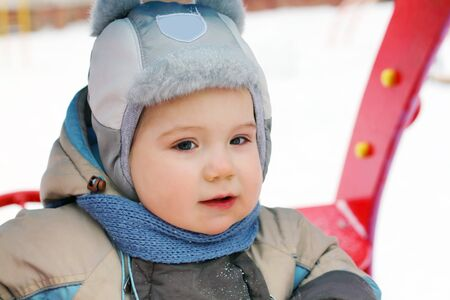 jumpsuit: Little boy wearing hat and jumpsuit play at playground at winter