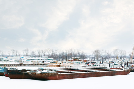 passenger ships: Old and rusty big freight and passenger ships on frozen river at winter cloudy day