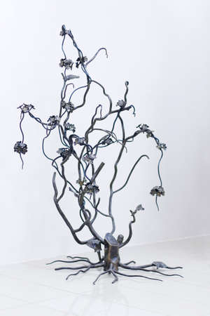 flower tree: Wrought sculpture blossom tree that grew out of old stump in white room Stock Photo