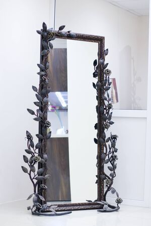 twined: Wrought frame twined with roses with mirror in white room