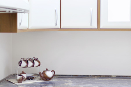 cupboards: Grey table with cups, teapots and cupboards in light and stylish kitchen Stock Photo