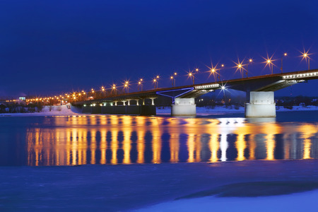 Bridge with lanterns and reflection in water of river with ice and snow at winter night