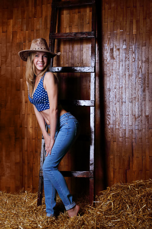 barefoot cowboy: Beautiful girl with blond hair wearing cowboy hat standing in hay by stairs