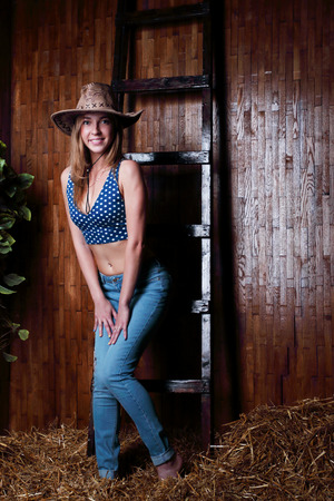 barefoot cowboy: Beautiful young girl with blond hair wearing cowboy hat standing in hay by stairs