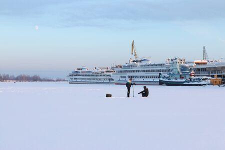 passenger ships: Two fishermen on frozen river on background of white passenger ships Stock Photo