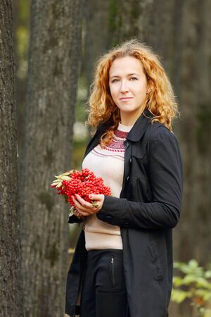 pit fall: Beautiful woman with red rowanberry smiles in autumn park at sunny day