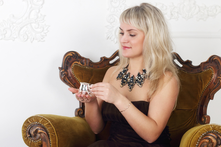 sits on a chair: Beautiful young woman sits in vintage chair and drinks coffee in white room