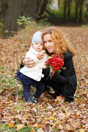 rowanberry: Beautiful woman with little daughter and rowanberry in autumn park at sunny day