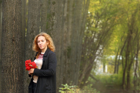 pit fall: Beautiful woman with red rowanberry stands in autumn park at sunny day Stock Photo