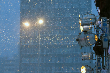 floodlights: Glowing floodlights illuminate snowflakes during snowfall in evening Stock Photo