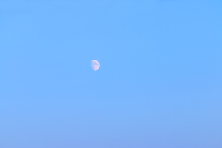 not full: White is not full moon on background of blue clear sky in evening time Stock Photo