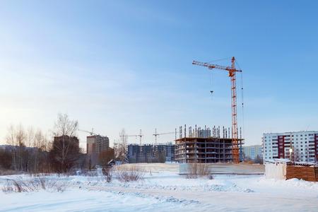 Large apartment buildings under construction in winter sunny day Foto de archivo