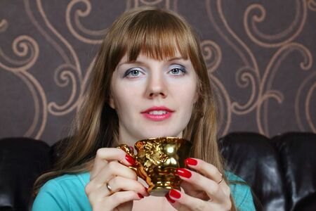 gilt: Young beautiful woman smiles and holds gilt cup on couch in room Stock Photo