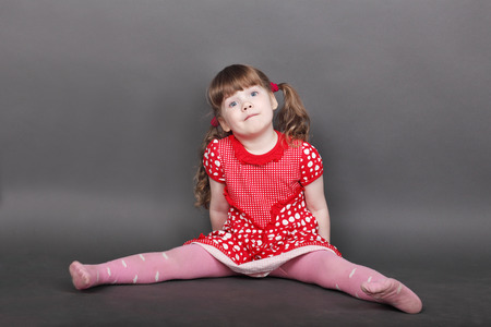 Funny little girl in red dress sits on floor in grey studio and looks at camera