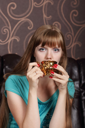 gilt: Young beautiful woman drinks coffee from gilt cup on couch in room