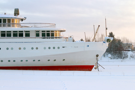 ship anchor: White and red prow of ship with an anchor in frozen river in winter day
