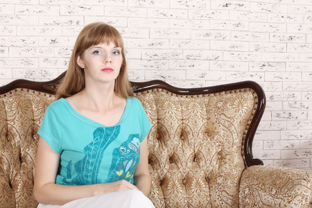 home comforts: Beautiful serious woman sits on couch and looks at camera in white room Stock Photo